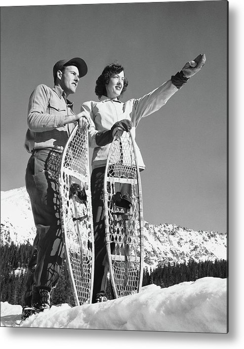 Heterosexual Couple Metal Print featuring the photograph Couple Holding Snowshoes, Woman Pointing by Stockbyte
