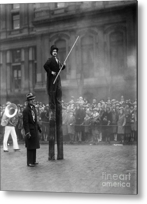 Crowd Of People Metal Print featuring the photograph Performer On Stilts by Bettmann