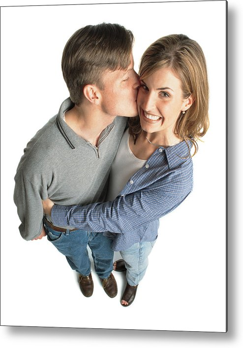 Young Men Metal Print featuring the photograph Young Couple With Brown Hair With The Boy Kissing The Girl On The Cheek And She Is Excited And Smiles by Photodisc