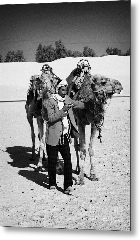 Tunisia Metal Print featuring the photograph Bedouin Camel Minder Recieves Call On A Mobile Phone With Camels In The Sahara Desert At Douz Tunisia by Joe Fox