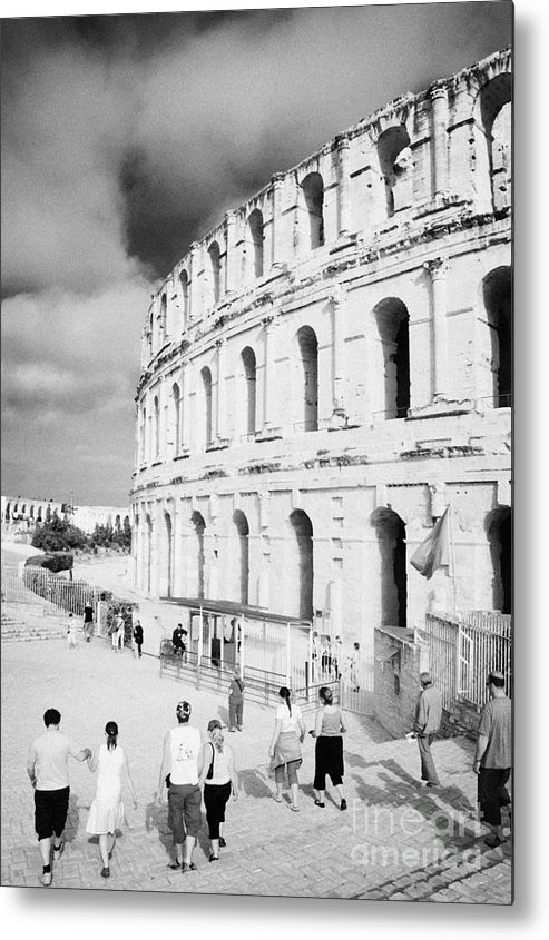 Tunisia Metal Print featuring the photograph Tourists Walk Down Steps Towards The Main Entrance Of The Old Roman Colloseum Against Blue Cloudy Sky El Jem Tunisia Vertical by Joe Fox