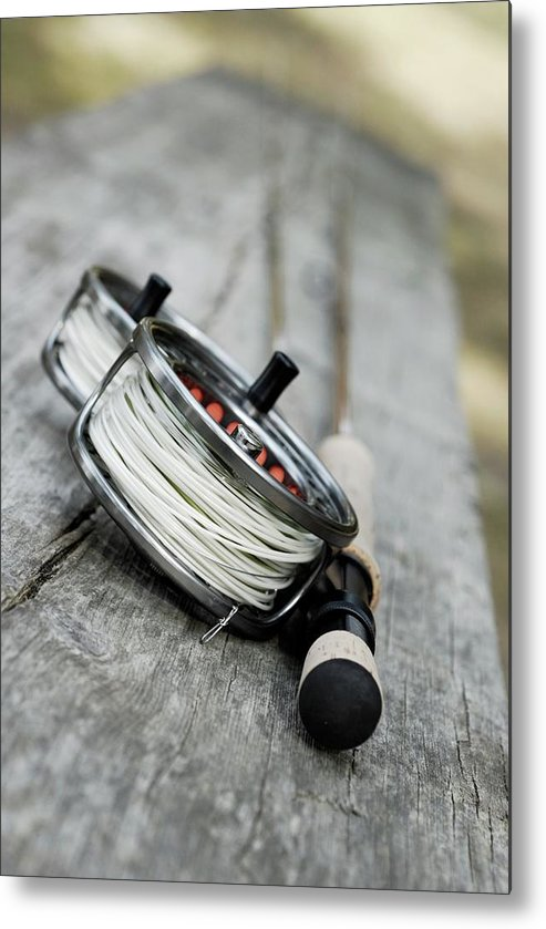 Two Objects Metal Print featuring the photograph Close-up Of Two Fishing Reels And A by Glowimages
