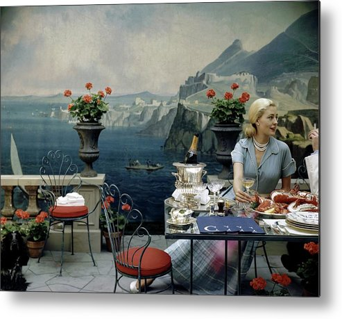 Exterior Metal Print featuring the photograph A Woman Sitting At A Dining Table In Front by John Rawlings