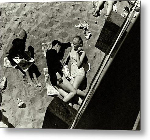 Swimwear Metal Print featuring the photograph A Young Couple Lying On A Beach by Lusha Nelson