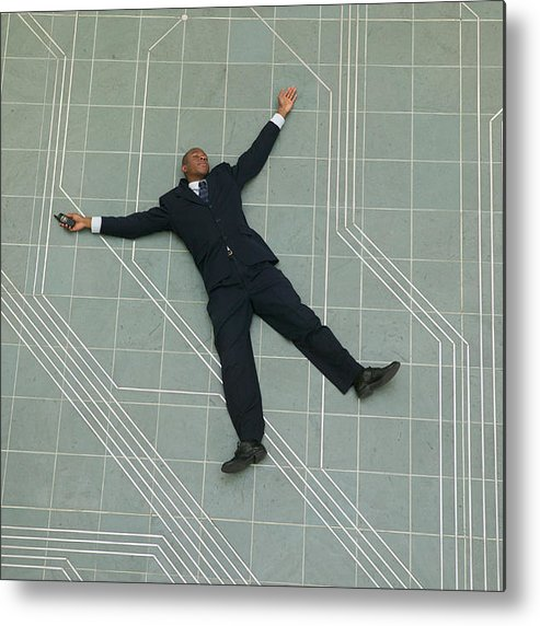 Corporate Business Metal Print featuring the photograph Conceptual Shot Of An African American Business Man As He Lays Flat On The Ground Holding His Phone by Photodisc