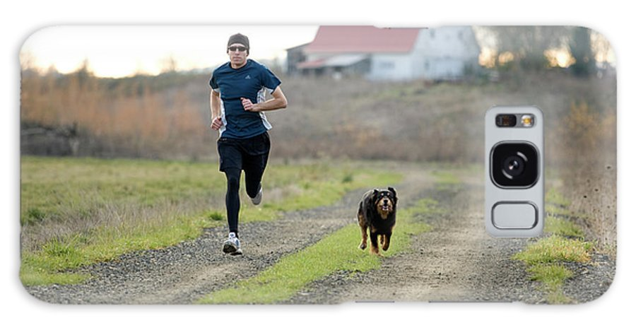 Active Galaxy Case featuring the photograph A Man And His Dog Jog Down A Country by Jordan Siemens