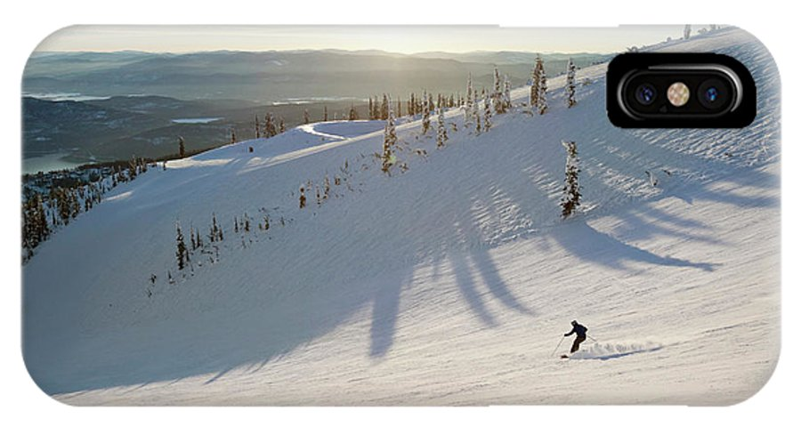 Extreme Sports IPhone X Case featuring the photograph A Lone Skier Makes A Turn At Whitefish by Craig Moore