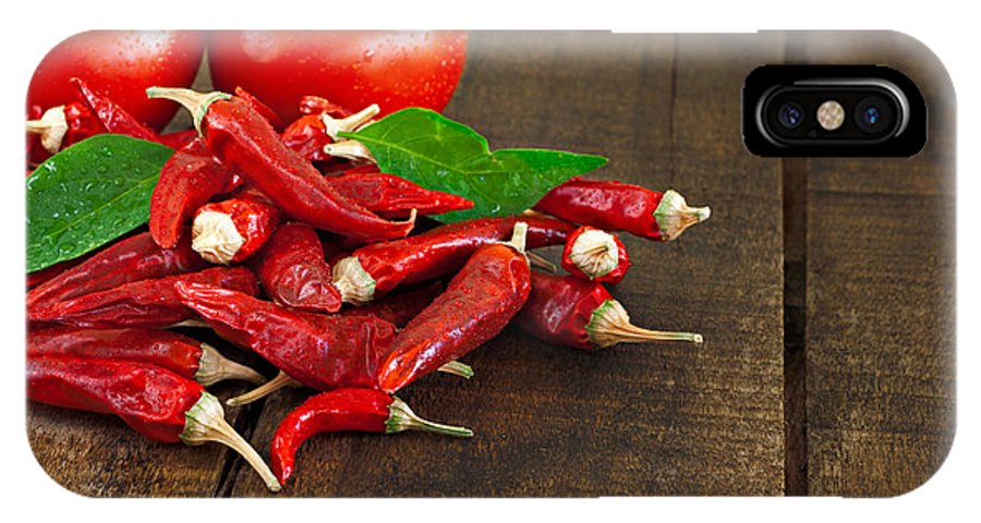 Chilli IPhone X Case featuring the photograph Dried Red Chillies And Tomato On A Rustic Wooden Table by Ken Biggs