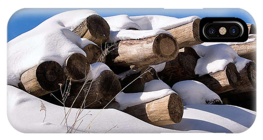 Log IPhone X Case featuring the photograph Log Pile In A Snow Drift In Winter by Louise Heusinkveld