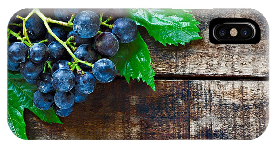Grape IPhone X Case featuring the photograph Purple Grapes On A Rustic Wooden Table by Ken Biggs