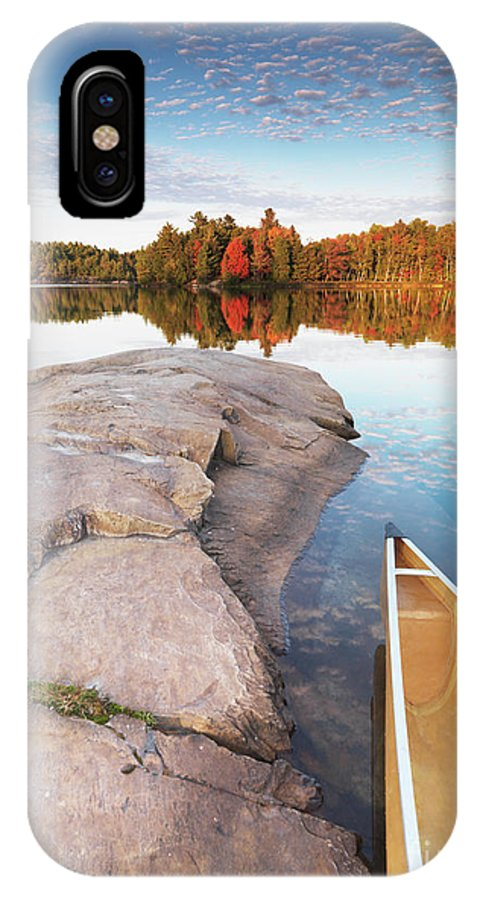 Canoe IPhone X / XS Case featuring the photograph Canoe At A Rocky Shore Autumn Nature Scenery by Oleksiy Maksymenko