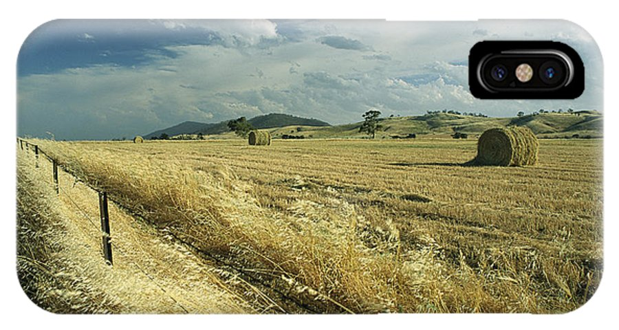 Clouds IPhone X / XS Case featuring the photograph A Hay Field With Bales Sitting by Medford Taylor