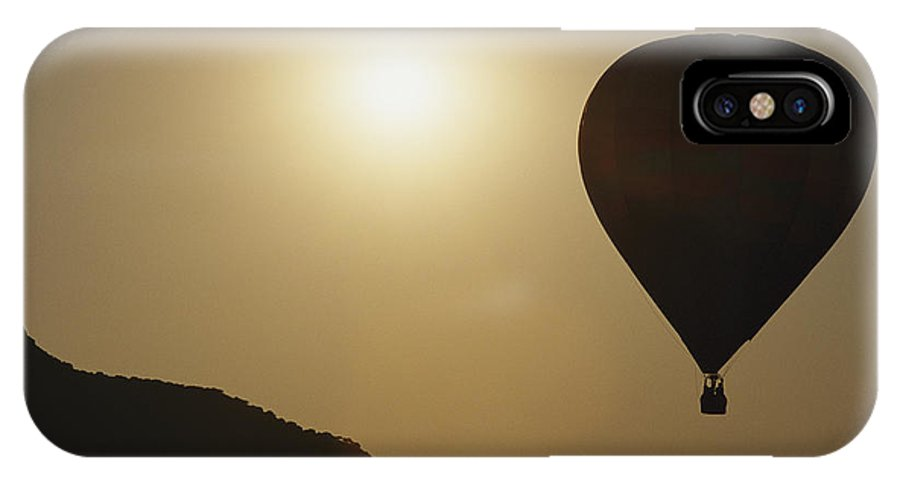 Scenes And Views IPhone X / XS Case featuring the photograph A Hot Air Balloon Rises Above A Hilly by Raul Touzon