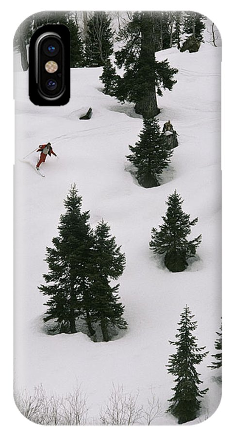 Asia IPhone X / XS Case featuring the photograph A Skier Makes His Way Down A Hill by Gordon Wiltsie