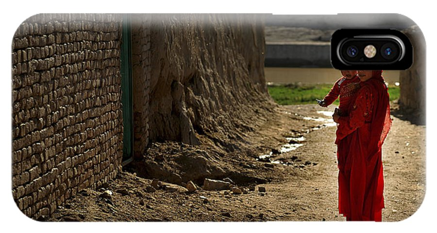 Qalat IPhone X Case featuring the photograph An Afghan Girl Carries Her Little by Stocktrek Images