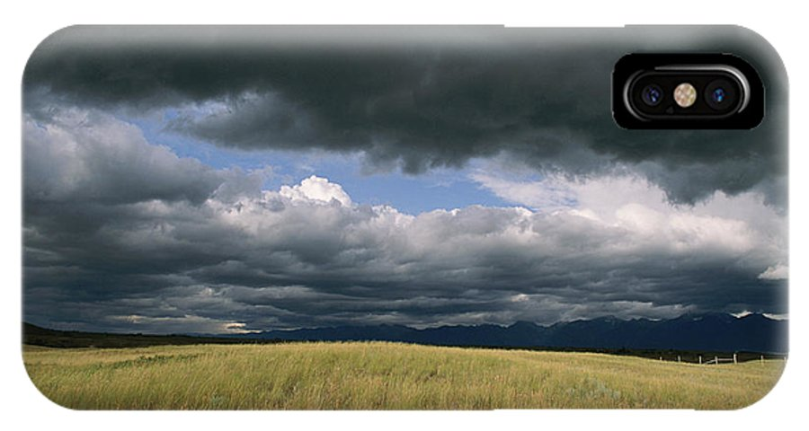 North America IPhone X / XS Case featuring the photograph Dark Clouds Gather Over A Prairie by Annie Griffiths