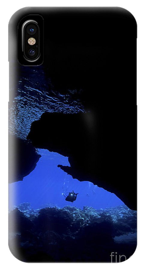 Diver IPhone X Case featuring the photograph Diver With Lights Entering A Submerged by Mathieu Meur