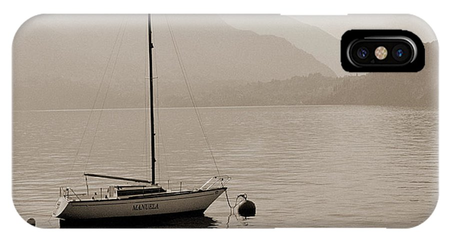 A Lone White Boat Sits Anchored On Lake Como With The Distant Hills Receding Into The Morning Haze. Sepia Tones Enhance The Composition Of This Photograph. IPhone X Case featuring the photograph Lone White Boat On Lake Como In Sepia by Greg Matchick
