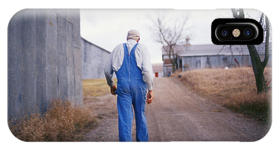 Scenes And Views IPhone X Case featuring the photograph An Elderly Farmer In Overalls Walks by Joel Sartore