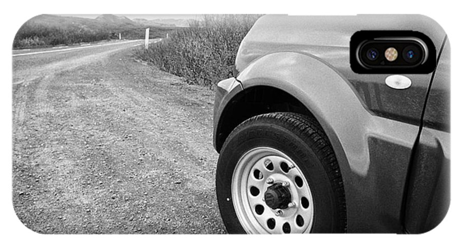 Wheel IPhone X / XS Case featuring the photograph Wheel Of Small 4x4 Vehicle Driving On Gravel Road Onto Main Road Reykjavik Iceland by Joe Fox