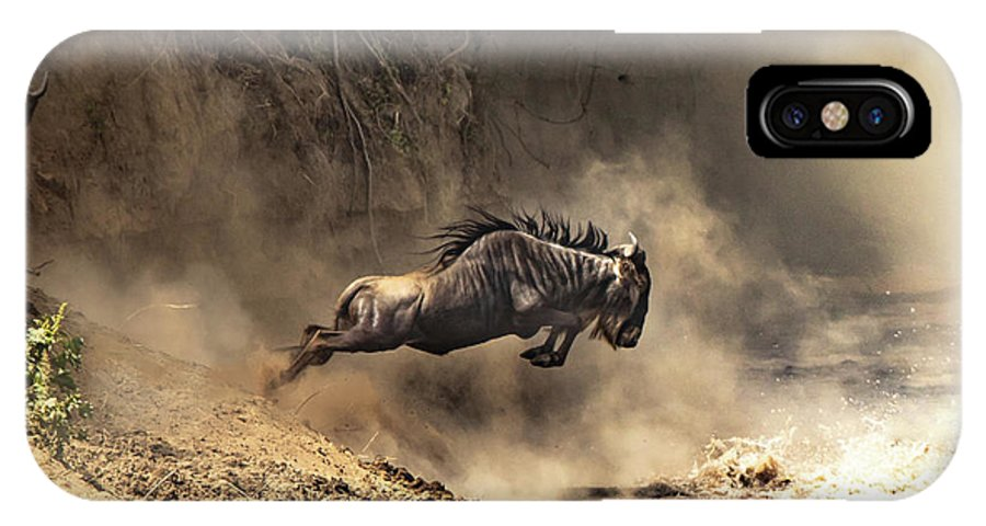 Mara IPhone X Case featuring the photograph Wildebeest Leaps From The Bank Of The Mara River by Jane Rix