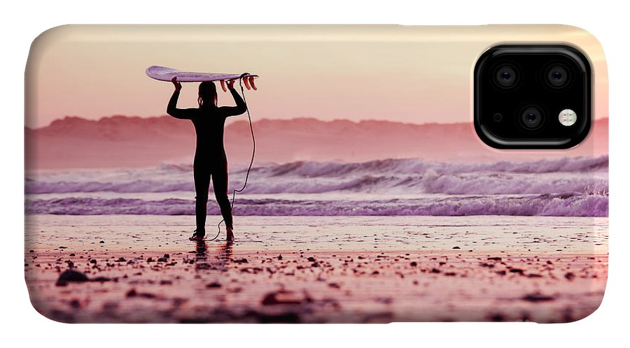 Sunrise IPhone 11 Case featuring the photograph Female Surfer On The Beach At The Sunset by Iko