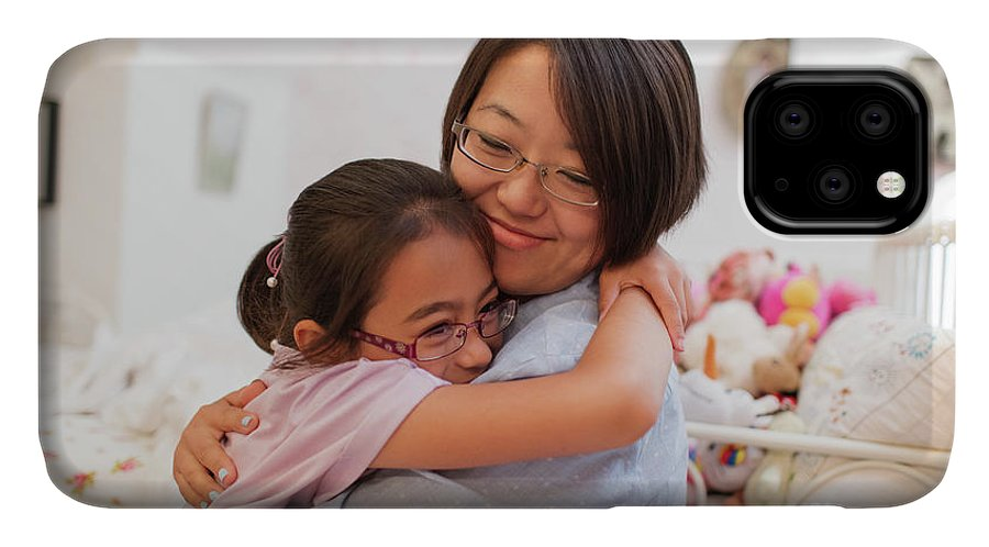30-34 Years IPhone Case featuring the photograph Mother And Daughter Hugging In Bedroom by Caia Image/science Photo Library