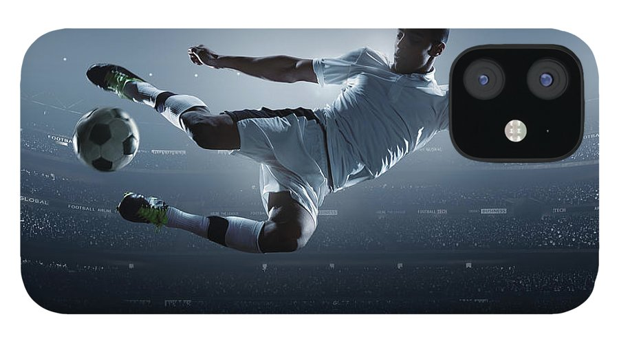 Goal IPhone 12 Case featuring the photograph Soccer Player Kicking Ball In Stadium by Dmytro Aksonov