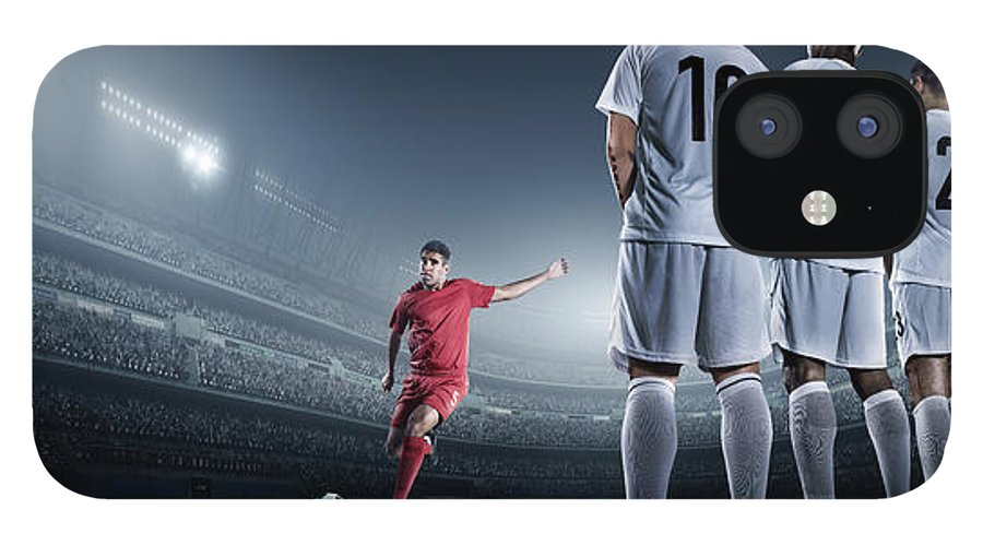 Soccer Uniform IPhone 12 Case featuring the photograph Soccer Player Kicking Ball In Stadium by Dmytro Aksonov