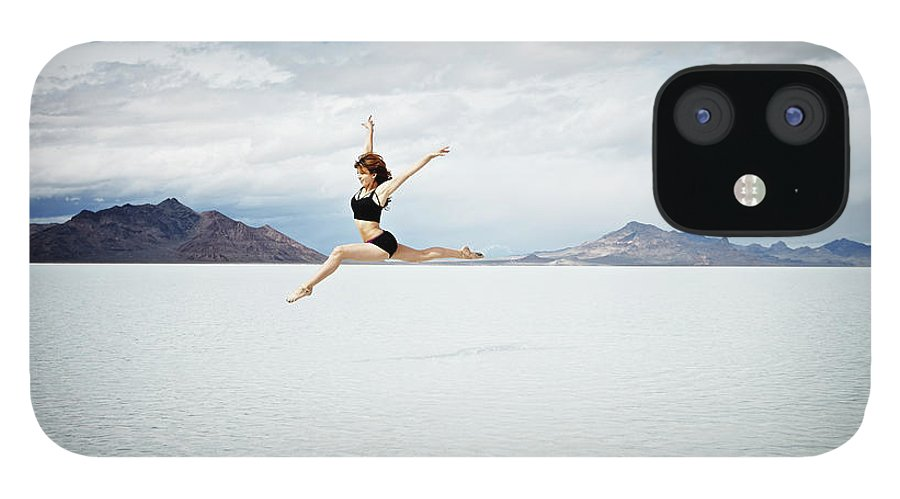 Ballet Dancer IPhone 12 Case featuring the photograph Ballerina Leaping In Mid-air Over Lake by Thomas Barwick