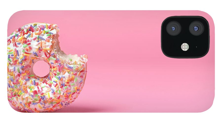 Unhealthy Eating IPhone 12 Case featuring the photograph Doughnut On Pink With Bite Out by Peter Dazeley