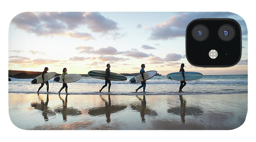 Young Men IPhone 12 Case featuring the photograph Five Surfers Walk Along Beach With Surf by Dougal Waters