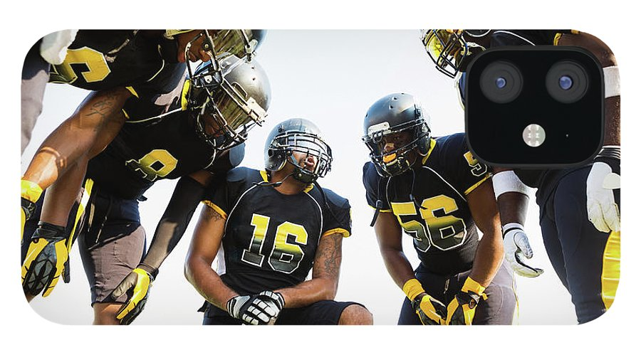 Young Men IPhone 12 Case featuring the photograph Football Team Huddled During Time Out by Asiseeit