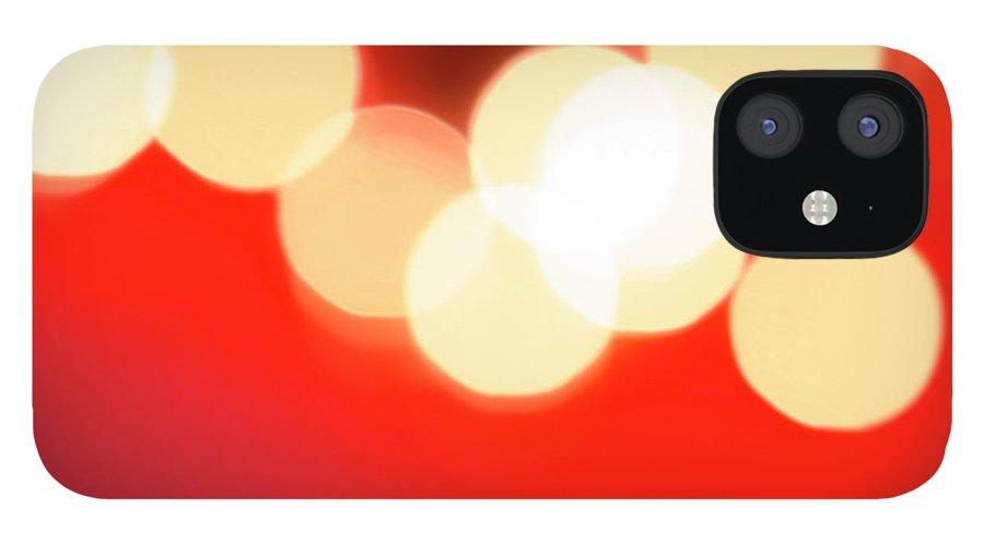 Christmas Lights IPhone 12 Case featuring the photograph Glowing Light On Red Background, Studio by Tetra Images