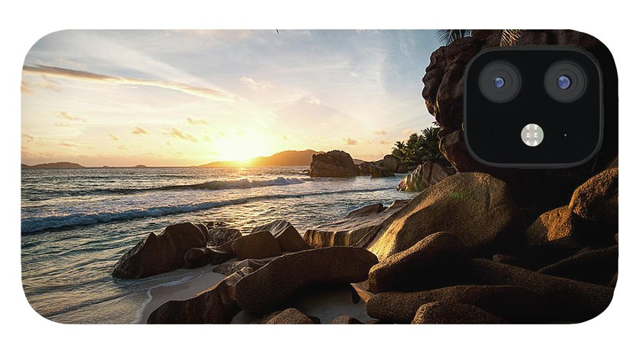 Water's Edge iPhone 12 Case featuring the photograph Sunrise Framed By Palm Trees And Rock by Pitgreenwood