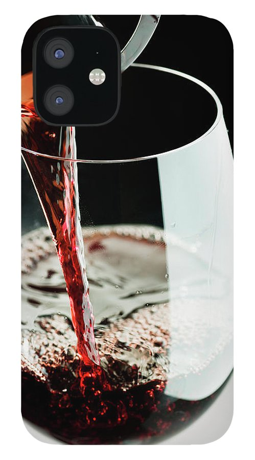 Alcohol IPhone 12 Case featuring the photograph Red Wine Being Poured In A Glass by Juanmonino