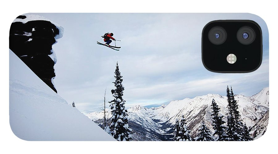 Skiing IPhone 12 Case featuring the photograph A Athletic Skier Jumping Off A Cliff In by Patrick Orton