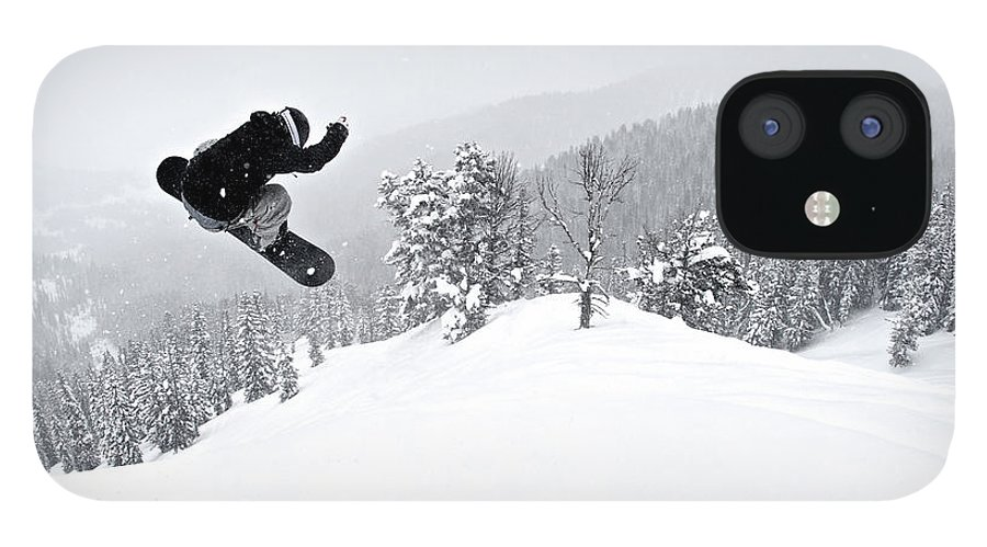 Recreational Pursuit IPhone 12 Case featuring the photograph A Man On A Snowboard Flies Through The by Derek Diluzio