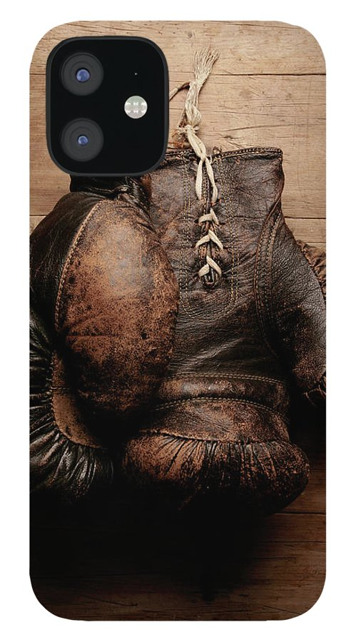 Hanging IPhone 12 Case featuring the photograph A Pair Of Worn Old Boxing Gloves On by The flying dutchman