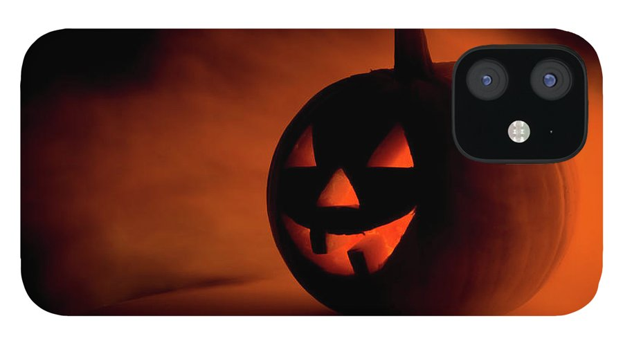 Horror IPhone 12 Case featuring the photograph A Scary Halloween Pumpkin In Smoke by Ilonabudzbon
