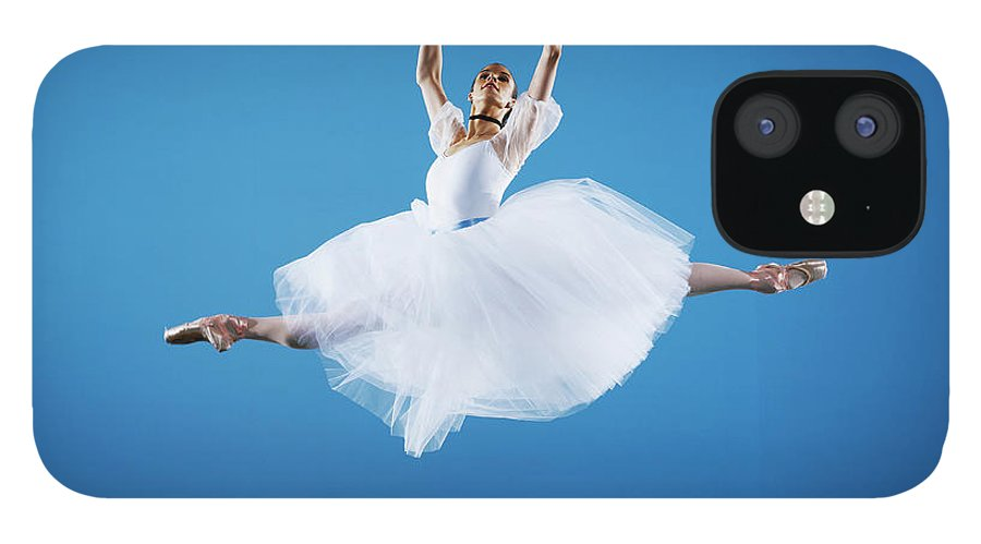 Ballet Dancer IPhone 12 Case featuring the photograph Ballerina Leaping On Stage, Arms Raised by Thomas Barwick