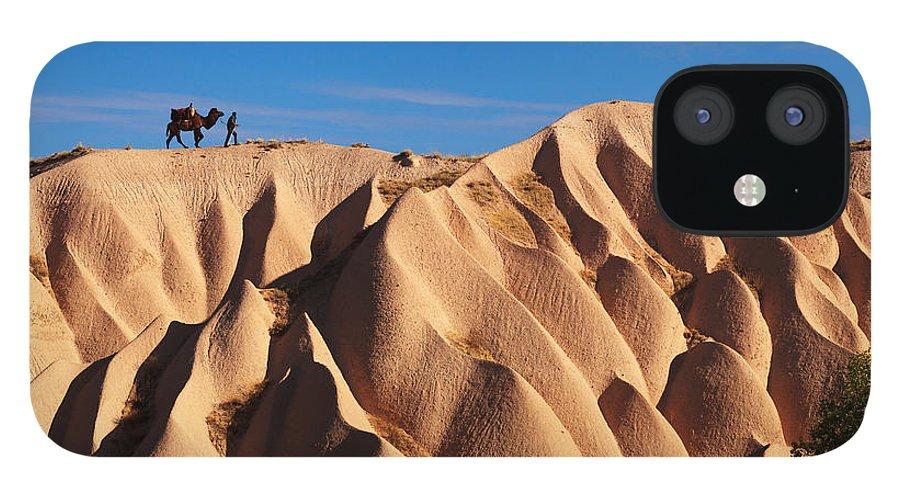 Kapadokya IPhone 12 Case featuring the photograph Camel And The Cameleer On The Rock by Yavuz Sariyildiz