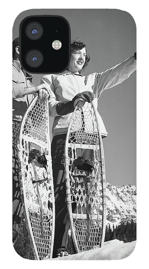 Heterosexual Couple IPhone 12 Case featuring the photograph Couple Holding Snowshoes, Woman Pointing by Stockbyte