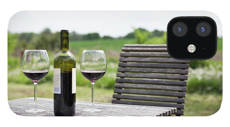 Five Objects IPhone 12 Case featuring the photograph Glasses And A Bottle Of Red Wine On An by Halfdark