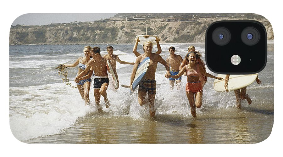Young Men IPhone 12 Case featuring the photograph Group Of Surfers Running In Water With by Tom Kelley Archive