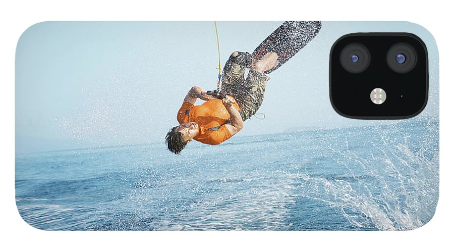 One Man Only iPhone 12 Case featuring the photograph Man Performing Wakeboarding Stunt At Sea by Paul Bradbury
