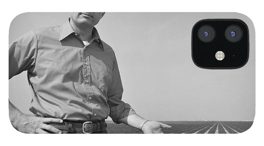 Mature Adult IPhone 12 Case featuring the photograph Mature Man Gesturing At Ploughed Field by Tom Kelley Archive