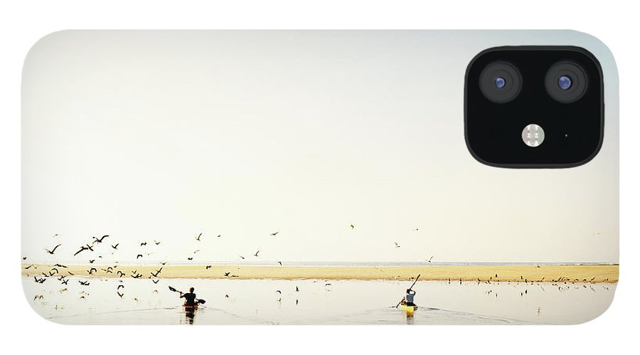 People IPhone 12 Case featuring the photograph Men Paddling Kayaks To The Beach by Julien Capmeil