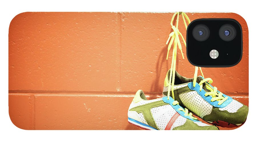 Hanging IPhone 12 Case featuring the photograph Runnig Shoes Hanging On A Hook by Pascalgenest