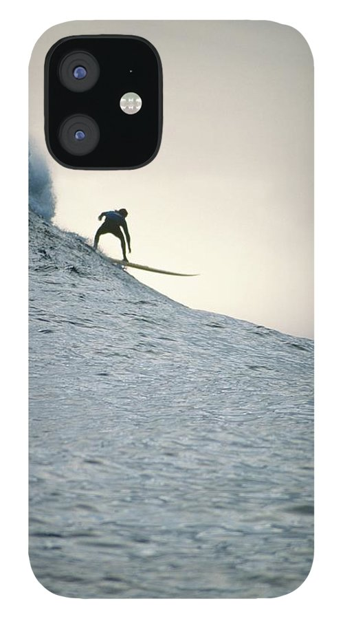 Scenics IPhone 12 Case featuring the photograph Silhouette Of A Surfer Riding A Wave by Dominic Barnardt